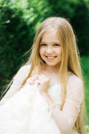 prom queen: small girl kid with long blonde hair and pretty smiling happy face in prom princess white dress standing in garden with green grass sunny day outdoor