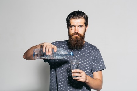 Handsome man young bearded male pours drinking water from bottle into glass on grey wall