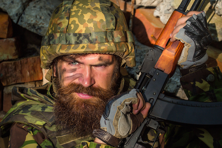 standoff: Soldier man with young bearded wicked angry dirty face in military helmet on head and rifle in hands wearing army ammunition sitting in stone brick ruins Stock Photo