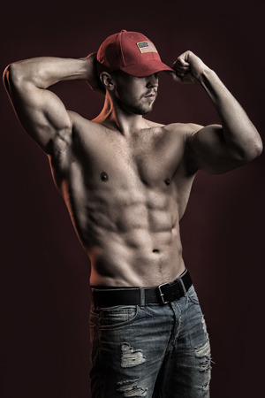 One sexual strong young man with muscular body in red sport  cap standing posing in studio on red background, vertical picture