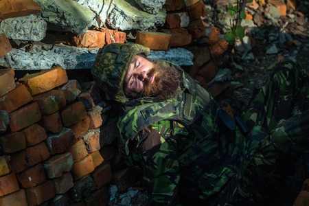 standoff: Killed soldier with beard on face in camouflage and military helmet on stone brick background
