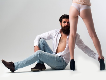 handsome bearded man with long beard on serious face sitting near sexy female legs and buttocks in lingerie and shoes of young pretty girl in studio isolated on white background, copy space