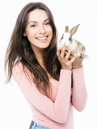 animal woman: young woman or girl with pretty smiling face with long hair in pink shirt holding little rabbit fluffy domestic animal pet isolated on white background Stock Photo