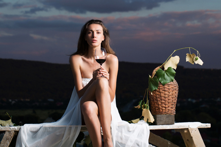 denuded: Beautiful girl in white sexy dress denuded gorgeous body with red wine glass wicker bottle and vine on evening nature over dramatic sky
