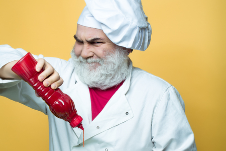catsup bottle: Bearded chef with ketchup bottle and grimace face in white uniform and hat on yellow background