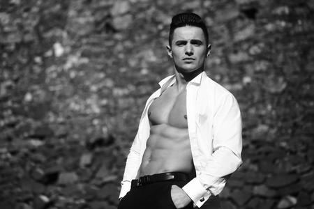 poses de modelos: El hombre joven y guapo modelo sensual con el torso desnudo en camisa se abría posturas abiertas con las manos en el bolsillo del pantalón fuera de blanco y negro en el fondo de mampostería Foto de archivo