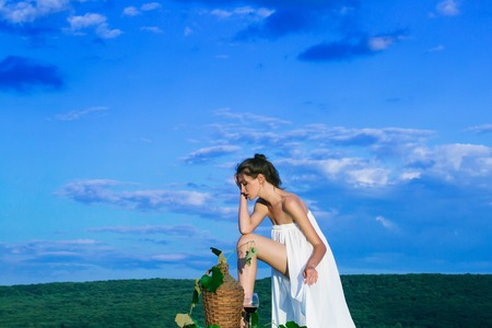 denuded: Beautiful girl in white dress denuded with red wine in glass wicker bottle and vine on nature over blue sky Stock Photo