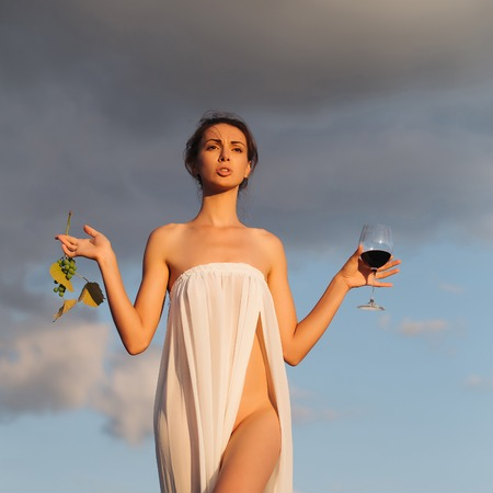 Pretty young girl or woman in white sexy dress denuded with red wine in glass and grapes on nature over blue sky Stock Photo