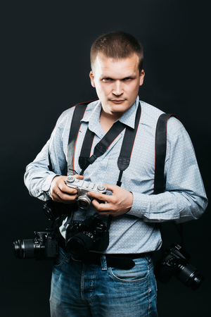 correspondent: young handsome man photographer with serious face in shirt with many photo cameras equipment of journalist or reporter professional in studio on black background Stock Photo