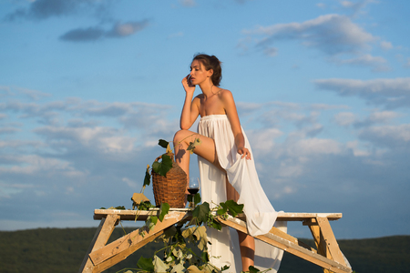 denuded: Beautiful girl in white sexy dress denuded with red wine in glass wicker bottle vine and grapes on nature over blue sky Stock Photo
