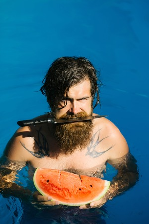 young knife: young bearded man with wet hair and beard swimming in pool with blue water holds knife and green red watermelon sunny summer day outdoor