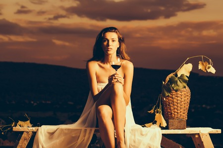 Beautiful girl in sexy dress denuded gorgeous body with red wine glass wicker bottle and vine on evening nature over dramatic sky
