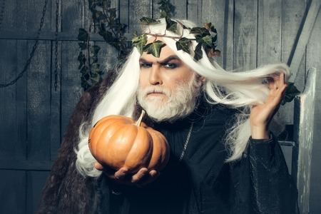 sorcery: Fairytale grey-haired old sorcerer with wreath of ivy and squash listen holding up long hair in wooden house