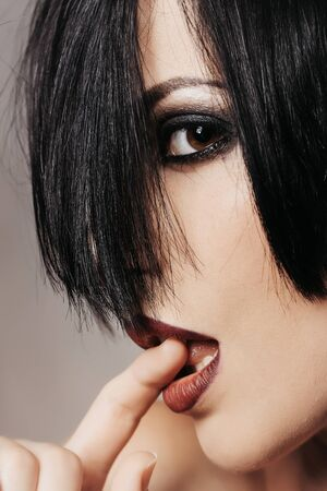 Pretty woman lady vamp brunette with brown smoky eyes and dark lips with finger in mouth on grey wall Stock Photo