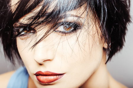 glamour makeup: young woman or girl with stylish short brunette hair and fashionable glamour makeup on pretty face portrait has bright lipstick on lips