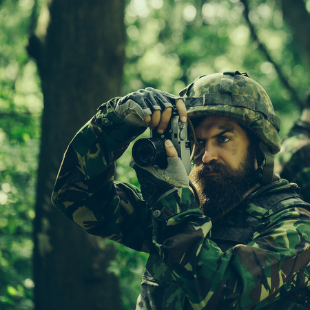 grime: Young soldier man with beard on grime serious face in ammunition and helmet holding camera in his hands on background of soldiers in forest