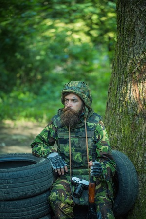 Young soldier wirh bearded dusty tired face in military camouflage uniform with hanging camera and rifle in hand sitting on guard near tree and black tyres in forest Stock Photo