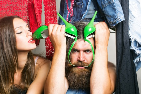 denuded: Fashion couple denuded tired of brunette girl with long hair and bearded man with green high heels shoes among clothes to wear near rack in closet Stock Photo