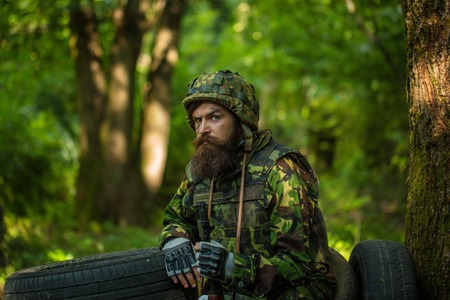face guard: Young soldier wirh bearded dusty tired face in military camouflage uniform with hanging camera and rifle in hand sitting on guard near tree and black tyres in forest Stock Photo