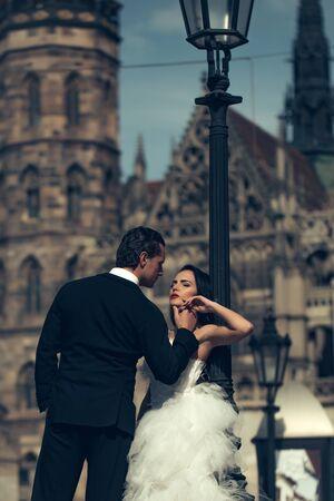 Junge Brautpaar von Mädchen mit brünetten Haaren und hübsches Gesicht in weißen Brautkleides und gut aussehender Mann in Anzug schwarz Bräutigam in der Nähe von Straßenlaterne auf Schloss oder Palast Gebäude sonnig im Freien stehen Standard-Bild - 63007665