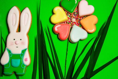 colorful tasty baked biscuits or sweet cookies in shape of hare or rabbit and heart for valentines day with grass on green background