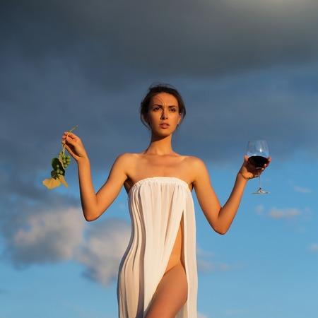 Bastante joven o mujer en vestido sexy blanco denudado con vino tinto en vidrio y uvas en la naturaleza sobre el cielo azul Foto de archivo - 63007780
