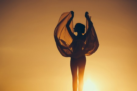 Silhouette of slim girl young woman female model dances in transparent windy dress on nature over beautiful sunset Stock Photo