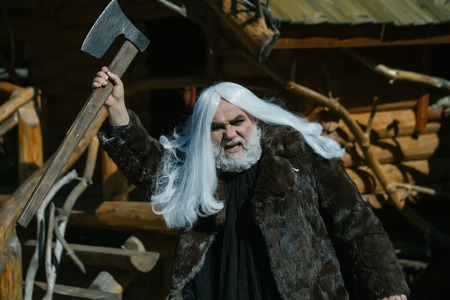 log house: Brutal druid old man with long silver hair and beard in fur coat with axe in hand on log house background Stock Photo