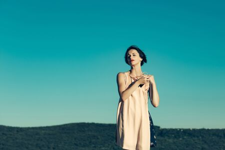 undressing woman: young brunette woman with pretty face and short hair undressing sunny day on nature on blue sky background, copy space