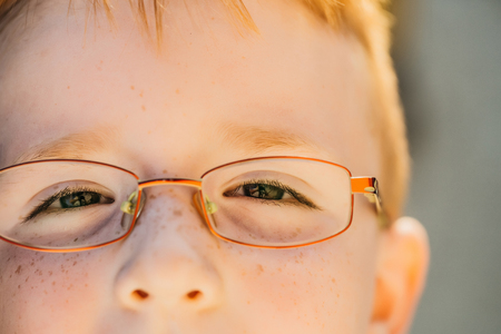 Cute little boy with freckled face and red hair in eyeglasses outdoors on sunny summer day Stock Photo
