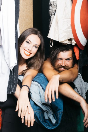 denuded: Fashion couple denuded of brunette girl and bearded man choose clothes to wear near rack in wardrobe closet Stock Photo