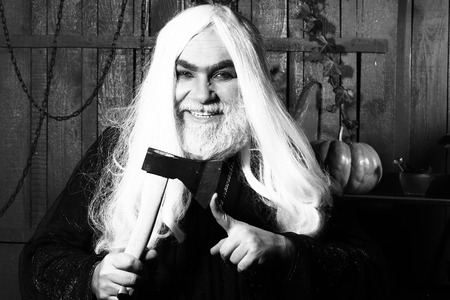 hatchet man: Old man witch in robe with demonic grin hold hatchet near finger in wooden house, black and white Stock Photo