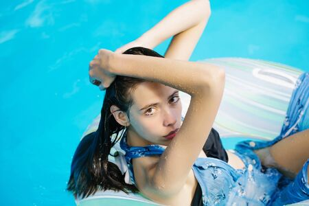 rubber ring: young woman or girl with pretty face and wet hair swimming in pool on rubber ring with blue water sunny summer day outdoor