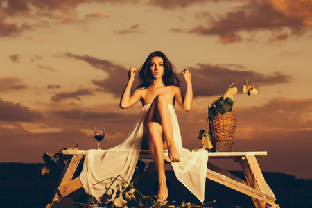 Beautiful girl in white sexy dress denuded gorgeous body with red wine glass wicker bottle and vine on evening nature over dramatic sky