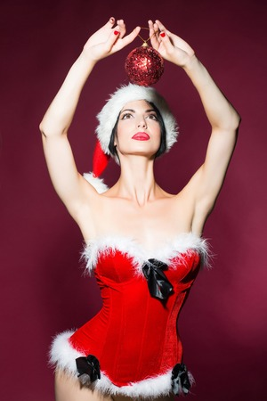 costume ball: young new year woman or girl with and red lips on pretty face in christmas santa claus hat and holiday costume holds decorative ball in studio on purple background Stock Photo