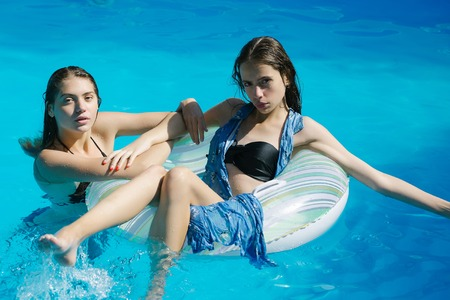 rubber ring: young women or girls with pretty face and wet hair swimming in pool on rubber ring with blue water sunny summer day outdoor