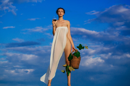 denuded: Pretty young girl or woman in white sexy dress denuded with red wine in glass wicker bottle vine and grapes on nature over blue sky