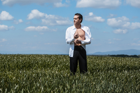 the stands: Handsome man businessman in open white shirt stands in green grass field on blue sky background