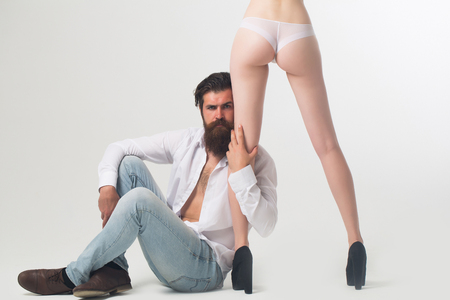 man ass: handsome bearded man with long beard and moustache on serious face sitting near sexy female legs and buttocks in lingerie and shoes of young pretty girl in studio isolated on white background