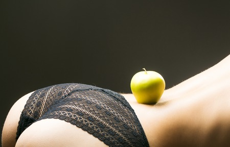 Sexy woman buttocks in black lace panties lingerie with yellow apple on beautiful denuded curvy back on dark background