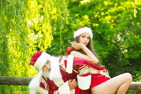 크리스마스 새 해 붉은 양복과 모자에 웃는 산타 클로스 남자와 예쁜 여자 자연 배경에 포즈 야외