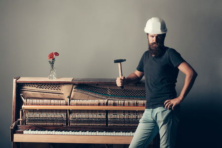 grand hard: handsome bearded man worker with beard in building helmet or hard hat holds hammer near wooden or wood piano with keyboard and glass vase with red rose flowers on grey background, copy space Stock Photo