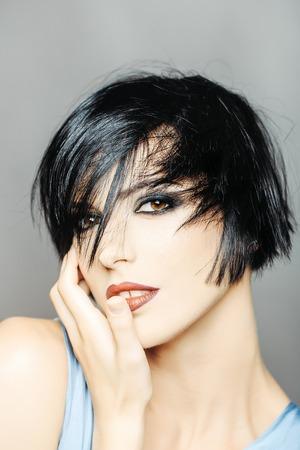 jonge vrouw of meisje met stijlvolle korte brunette haar en modieuze glamour make-up op mooie lachend gezicht portret heeft felle lippenstift op de lippen
