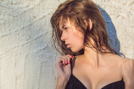 cleavage: Young woman with pretty face healthy skin and wet brown hair in black swimsuit with cleavage posing in summer on white wall background