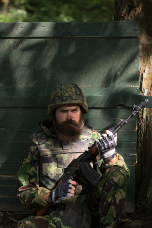 aggressiveness: Young soldier hipster with tired bearded face in military ammunition armed with rifle in hands sitting leaned on wooden green shield