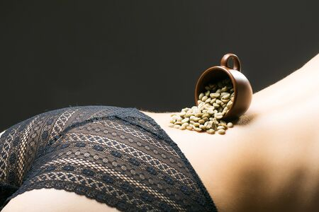 Sexy woman buttocks in black lace panties with cup of coffee beans on beautiful denuded curvy back on dark background Stock Photo