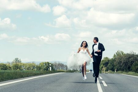 happy wedding: young wedding happy couple of girl with brunette hair and pretty face in white bride dress and handsome man in black groom suit running on road way on cloudy blue sky background, copy space Stock Photo