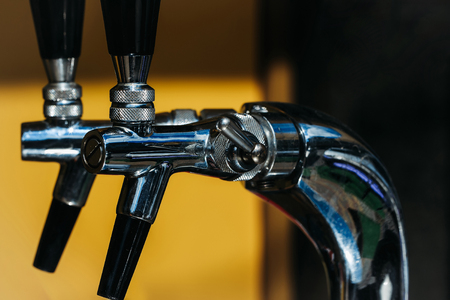 Bright metal taps regular chrome faucets for draught beer drink water or alcohol liquid in pub on yellow background