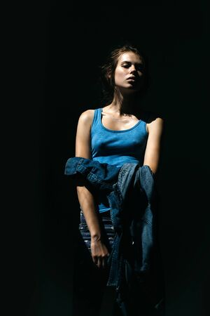 undershirt: Attractive young woman in blue undershirt and jeans poses in studio on dark grey wall