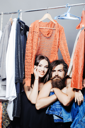 denuded: Fashion couple denuded of brunette girl and bearded man choose clothes to wear near rack with hangers in wardrobe closet